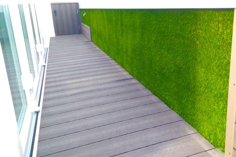Pared de césped artificial con suelo de madera sintética